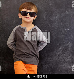 Portrait of smart little boy wearing sunglasses smirking. Cool kid in shades leaning on a blackboard looking at - Stock Photo