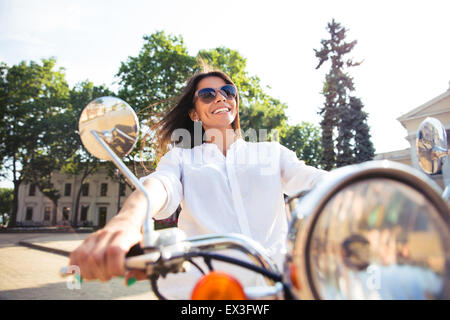 Smiling young girl driving scooter in the city - Stock Photo
