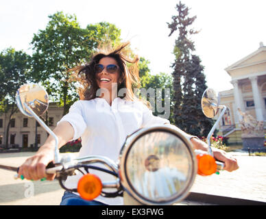 Cheerful cute woman driving scooter in old european town - Stock Photo