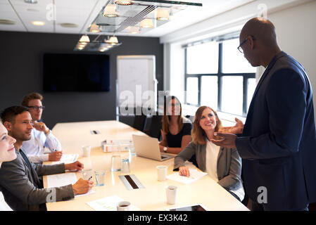 Black man leading a meeting with a group of executives in a conference room - Stock Photo
