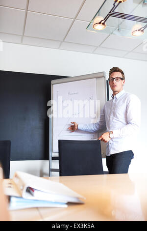 Young white male executive pointing to a chart on a whiteboard leading a meeting - Stock Photo