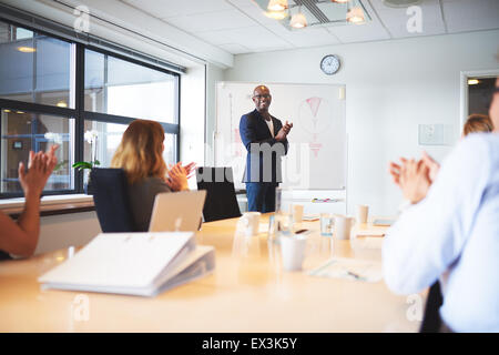 Black male executive standing at head of table in conference room smiling leading meeting - Stock Photo