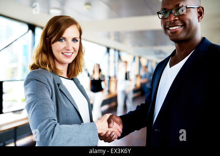 Close up of colleagues shaking hands smiling at camera - Stock Photo