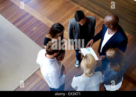 View looking down at colleagues standing in a circle looking at charts on paperwork - Stock Photo