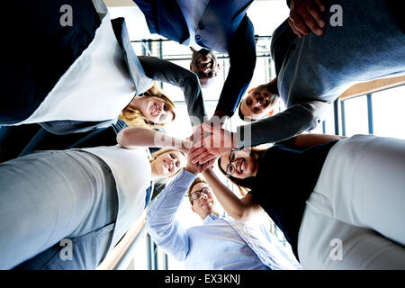 Group of young executives standing in a circle with hands together looking down. - Stock Photo
