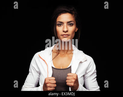 Shot of young fitness model posing in studio. Healthy young woman in sportswear standing against black background. - Stock Photo