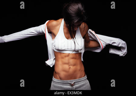 Image of muscular young woman wearing sports jacket. Getting ready for workout on black background - Stock Photo