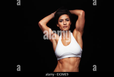 Attractive young woman in sportswear posing on black background. Healthy female model with muscular body in studio. - Stock Photo