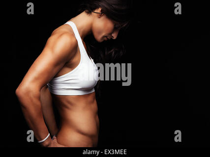 Side view of muscular fitness female model standing on black background. Young woman wearing sports bra looking - Stock Photo