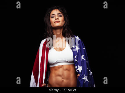 Portrait of proud female athlete wrapped in American Flag against black background. Muscular young woman looking - Stock Photo
