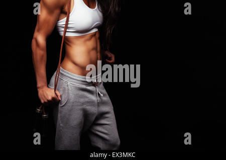 Close up of young woman's torso. Perfect abdomen muscles of a female athlete holding skipping ropes on black background - Stock Photo