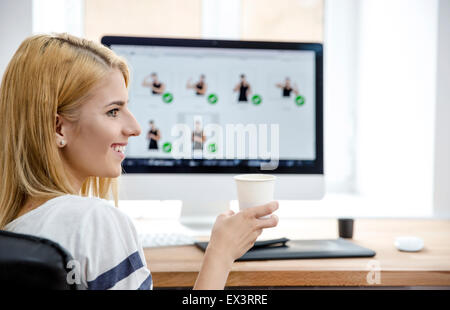 Happpy young woman sitting at the table in office and holding cup with coffee - Stock Photo