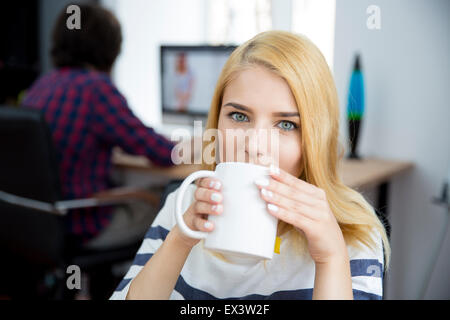 Young casual woman drinking coffee in office - Stock Photo