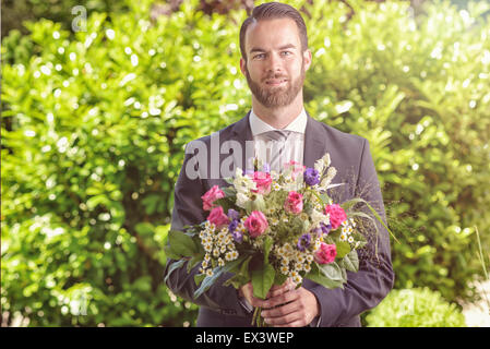 Handsome bearded young man in a suit carrying a bouquet of fresh flowers, possibly a suitor or beau calling on a - Stock Photo