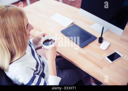 Top view portrait of a female photo editor sitting at the table and drinking coffee in office - Stock Photo