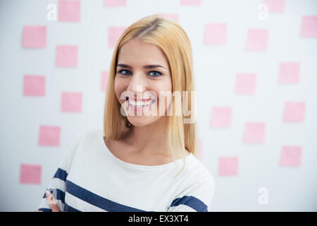 Cheerful young woman standing in office with stickers on background - Stock Photo