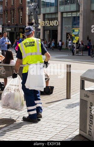 Worker from Leeds City Council City Centre Cleansing Team emptying bins and collecting rubbish on Briggate near - Stock Photo