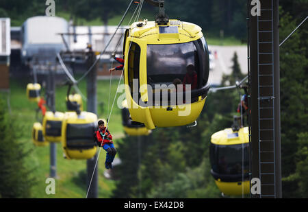 Schoenau, Germany. 19th June, 2015. Members of the mountain rescue services rope down from a Belchen gondola lift - Stock Photo