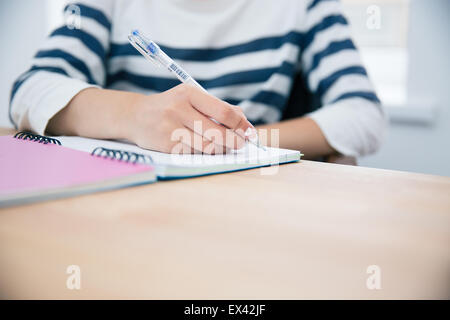 CLoseup portrait of a woman writing in notepad at office - Stock Photo