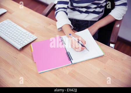 Closeup portrait of a casual woman writing notes in office - Stock Photo
