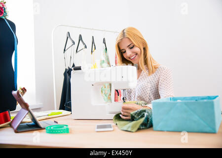 Happy female tailor using sewing machine in laundry - Stock Photo