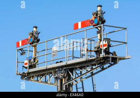 Old style mechanical semaphore stop signals on a British railway, both in the stop position, in England, UK. - Stock Photo