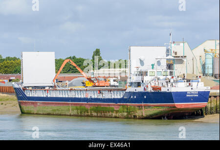 The cargo ship 'Victress' in port on a river being unloaded. - Stock Photo
