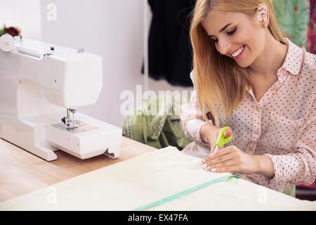Happy female designer cutting cloth in workshop - Stock Photo