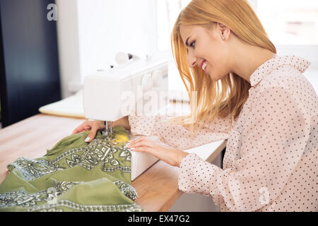 Side view portrait of a happy female deisgner using a sewing machine in workshop - Stock Photo