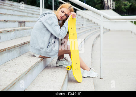Young girl resting with skateboard on the park stairs - Stock Photo