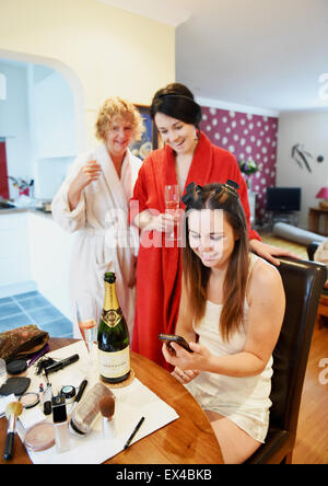 Young bride sitting surrounded by family as she prepares for the big day drinking champagne - Stock Photo