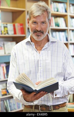 Portrait Of Male Customer Reading Book In Bookstore - Stock Photo