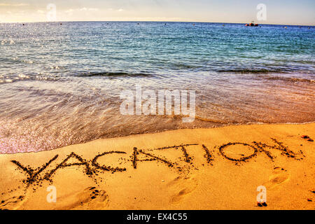Vacation holiday word in sand written on beach resort sea coast coastline holidays vacations trips trip getaway - Stock Photo