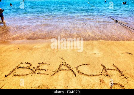 Beach word in sand written on beaches Spanish fun resort seas coast coastlines holidays vacations trips trip getaway - Stock Photo
