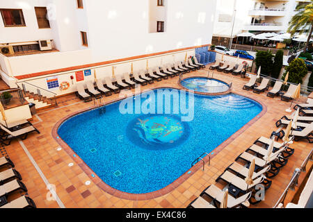 Hotel swimming pool from above sun loungers set out around edge Ibiza Spain Spanish resort vacation holiday destination - Stock Photo