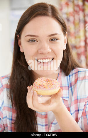 Portrait Of Smiling Teenage Girl On Eating Donut - Stock Photo