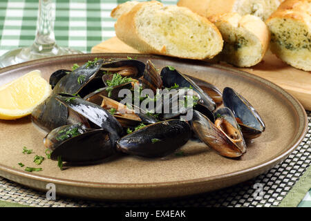 seafood mussels in white wine sauce with parsley and garlic bread - Stock Photo