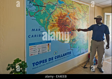 Horizontal view of a tour guide pointing out routes in Topes de Collantes National Park visitor centre in Cuba. - Stock Photo