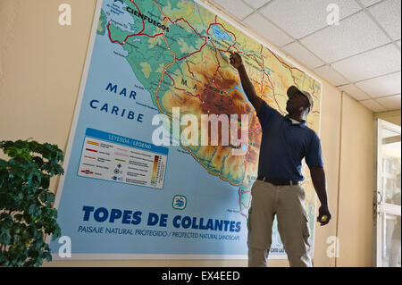 Horizontal view of a tour guide pointing at a map in Topes de Collantes National Park visitor centre in Cuba. - Stock Photo