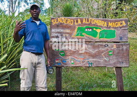Horizontal portait of a tour guide infront of an information board in Topes de Collantes National Park in Cuba. - Stock Photo