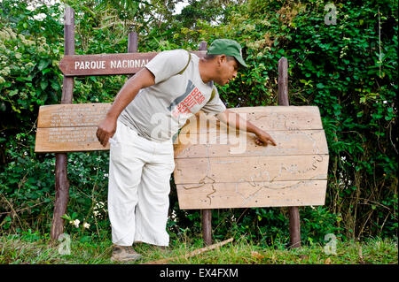 Horizontal portrait of a tour guide pointing out the trail in Turquino National Park, Cuba. - Stock Photo