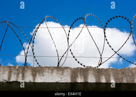 barbed wire on top of the concrete fence with blue sky with clouds closeup - Stock Photo