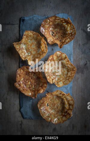 Walnut cornets on slate board on wooden background. Top view - Stock Photo