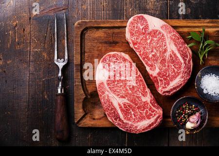 Two Raw fresh marbled meat Black Angus Steak Ribeye, seasonings and meat fork on dark wooden background - Stock Photo