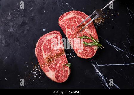 Two Raw fresh marbled meat Black Angus Steak Ribeye, seasonings and meat fork on dark marble background - Stock Photo