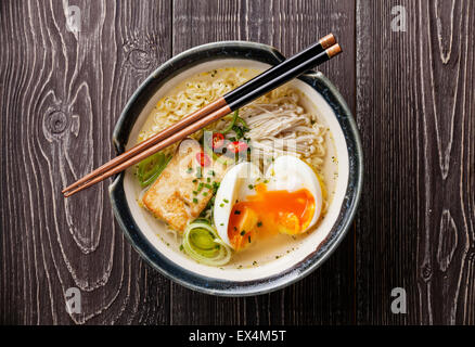 Asian Miso ramen noodles with egg, tofu and enoki in bowl on gray wooden background - Stock Photo