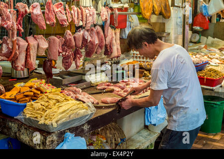 Butcher cutting meat at the food market in Hong-Kong - Stock Photo