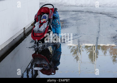 A little boy pushing a his baby sister's pushchair through a deep puddle - Stock Photo