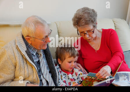 A toddler (3 yrs old) in pyjamas having a bedtime story with his grandparents - Stock Photo