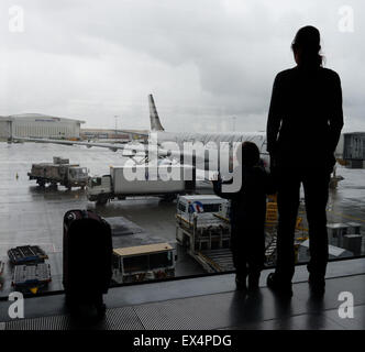 A young boy and his mum looking out of an airport window at the planes - Stock Photo